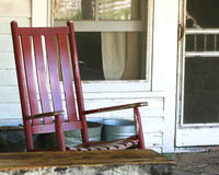 Red rocker on a farmhouse porch stock photo