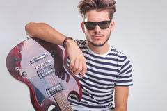 Rocker pose while resting on electric guitar in studio Stock Photography