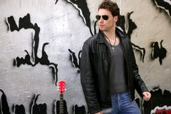 Rocker rock star young man sunglasses. On silver wall city outdoor stock image