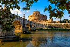 Rockera Sant Angelo Mausoleum av Hadrian, bron Sant Angelo och floden Tiber i strålarna av solnedgången i Roma Royaltyfri Bild