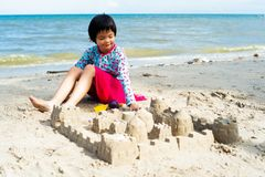 Rockerar asiatiska flickalekar för stående på stranden och bygganden arkivfoton