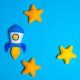 Rocket entfernt sich Handgemachte Filzspielwaren Raumschiff mit Gelb spielt auf lue Hintergrund die Hauptrolle Stockbild