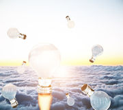Rocket fire lightbulbs at sunset. Creative business start up idea concept with abstract rocket fire lightbulbs in sky with clouds and setting sun. 3D Rendering Royalty Free Stock Photos