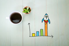 Rocket graph concept with a cup of coffee. On a pastel green wooden table Royalty Free Stock Photos