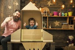 Rocket launch concept. Kid happy sit in hand made rocket. Boy play with dad, father, cheerful cosmonaut sit in rocket. Made out of cardboard box. Child cute boy stock image