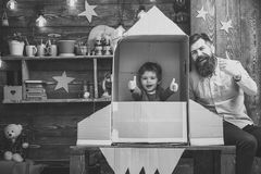 Rocket launch concept. Kid happy sit in hand made rocket. Boy play with dad, father, cheerful cosmonaut sit in rocket. Made out of cardboard box. Child cute boy royalty free stock photography