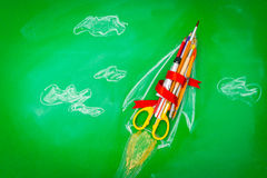 Rocket made from School supplies on Green chalkboard  Back to s Royalty Free Stock Photos