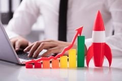 Rocket Beside Multi Colored Graph With Arrow. Rocket And Multi Colored Graph With Arrow In Front Of Businessperson Working On Laptop royalty free stock photos