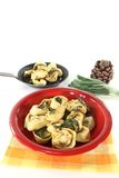 Rocket-ricotta tortellini with sage butter. Arugula and ricotta tortellini with sage butter and pine nuts on a light background royalty free stock image