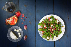 Rocket salad with cheese and pomegranate on rustic wood, view fr Stock Photo