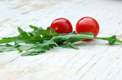 Rocket salad and cherry tomatoes. On a grunge table Royalty Free Stock Images