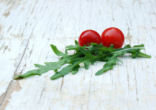 Rocket salad and cherry tomatoes. On a grunge table Stock Images