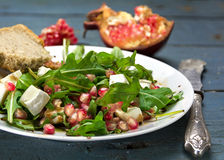Rocket salad with  feta cheese and pomegranate on an rustic wood Stock Image