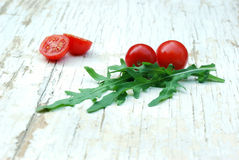 Rocket salad leaves and cherry tomatoes. Rocket salad and cherry tomatoes on a grunge table Stock Photo