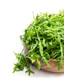 Rocket salad leaves in wooden bowl isolated on white. Rocket  salad leaves in wooden bowl isolated on white royalty free stock photo