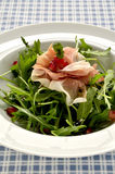 Rocket salad with parma ham and pomegranite seeds. A rocket salad with parma ham slices and pomegranite seed in a white bowl on a blue checked table cloth stock image