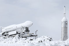 Rocket and shuttle covered in snow at a space museum