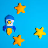 Rocket takes off. Hand made felt toys. Space ship with yellow stars on lue background. Stock Image