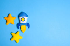 Rocket takes off. Hand made felt toys. Space ship with yellow stars on lue background. Stock Images