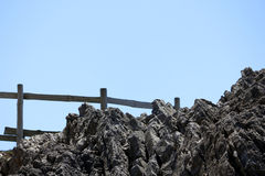 Rockfall with fence. A detailled rock with a pine wood fence and the sky as background Stock Photo
