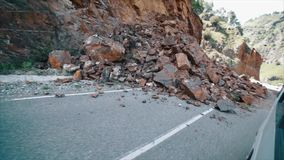 Rockfall op de weg stock footage
