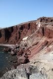 Rockfalls på den röda stranden av Santorini royaltyfria bilder