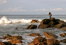 Rock fishing. Fisherman reeling in catch off rocks on Narrawallee Beach, NSW South Coast, Australia Stock Photography