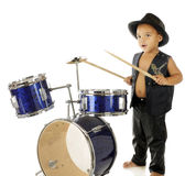 Rockin' Drummer Boy. An adorable, barefoot preschooler dressed as a rock star, beating on a drum set.  On a white background.  Motion blur on the drum sticks Royalty Free Stock Images