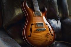 ` Rockin krzesła ` rocznika semi hollowbody akustyczna gitara elektryczna w rzemiennym krześle Obrazy Royalty Free