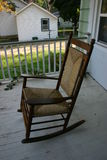Rocking Chair #3. A well worn rocking chair with a blanket thrown over the back on a white wooden porch Royalty Free Stock Photos