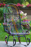 Rocking chair in the garden with flowers Stock Photos