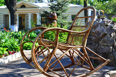 Rocking chair in the garden. Wicker rocking chair in a spring garden Stock Images