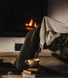 Rocking chair with knit rug, books and cup of tea or coffee before fireplace Stock Images