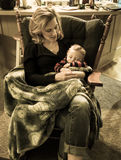 The Rocking Chair. A Mother Rocking Her Son to Sleep in A Chair Royalty Free Stock Photos