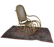 Rocking chair on old rug. Side view of antique rocking chair on old rug, white background royalty free stock photos