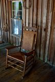 Rocking Chair on an Old-Time Front Porch. A rocking chair on the front porch of an old homestead house Royalty Free Stock Photo