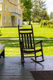 Rocking Chair on Old Village Porch. Lancaster, PA – July 13, 2016: A rocking chair on a porch on the grounds of the Landis Valley Village & Farm Museum Stock Image