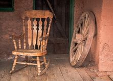Rocking chair and old wooden wheel in Calico ghost town in USA.  royalty free stock photography