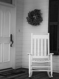Rocking Chair on Porch. Vintage scene of white rocking chair on front porch next to front door Royalty Free Stock Images