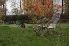 Rocking chair and wheelbarrow on the grass Royalty Free Stock Photo