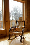 Rocking chair by window. Rustic wood rocking chair by window Royalty Free Stock Images