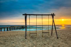 Seascape with Swinging Chairs on Beach and Ky Co Pier at Sunrise royalty free stock photography
