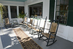 Rocking chairs on an outdoor porch. Many wood and wicker rocking chairs on a large outdoor front porch.  The porch is wood which has been painted and there is a Royalty Free Stock Photos