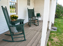 Rocking chairs overlooking a front yard. Two rocking chairs invite one to sit a while on this old porch Stock Photos
