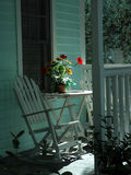 Rocking Chairs on Porch. Restful scene of rocking chairs and a table with a vase of flowers on a small porch in Key West, Florida Royalty Free Stock Photography