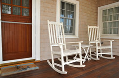 Rocking Chairs on Porch. Old fashioned white rocking chairs welcome visitors to sit on the front porch stock photo