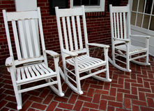 Rocking Chairs. Three white well-used old rocking chairs on brick porch Royalty Free Stock Images
