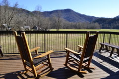 Rocking chairs. Two wooden rocking chairs from rear on porch overlooking Great Smoky Mountains Stock Image