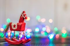 A Rocking horse with christmas lights on wooden background stock photos