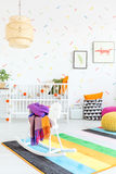 Rocking horse and cradle. White wooden rocking horse and cradle in a stylish baby room royalty free stock photography